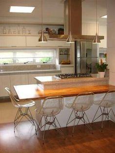 Cozinha bancada em madeira e cadeiras em acrílico transparentes.