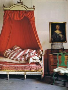 Lars Sjoberg's 18th Swedish Manor House. White and gold painted Gustavian bed with red cotton canopy