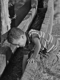 Boy reaching into an irrigation canal at A. Fakhry & Co. | Crafters of Aromatic Raw Materials, Egypt