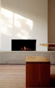 interior by John Pawson. private home, wooden bench, stone fireplace. minimalist interior