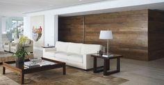 No living do duplex em São Conrado (RJ), com revestimento em madeira de demolição nas paredes e porta de entrada, o sofá na cor branca dá um contraste harmonioso ao ambiente. O projeto de reforma e interiores é de autoria da arquiteta Izabela Lessa