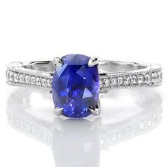 The magnetic color of this 1.50 carat cushion cut sapphire is a perfect focal point on this graceful, vintage-inspired ring. The top of the band is adorned with bead set diamonds while the sides are handsomely appointed with hand engraving, filigree, and three petals with diamonds delicately placed.   #engagement #wedding #ring www.knoxjewelers.biz