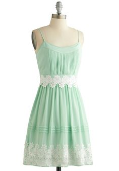 This dreamy, pastel mint A-line dress is not a figment of your imagination! From the dainty, adjustable shoulder straps to the bright white lace appliques at the empire waistline and hem, the details of this frock create a vision of elegance. This fully lined dress features a lightly padded bust and an extra layer of shimmery organza lining beneath its skirt, which creates a delicate, glimmering effect. Pair this piece with a pearl necklace and white heels, and enjoy a special occasion in…