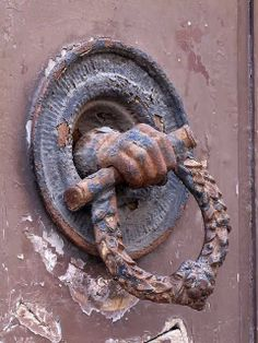 "Interesting a hand coming out of the door in a metal disc holding a ""scroll?"" and wreath with lion's head - Front door handle, via Ricasoli, Livorno"