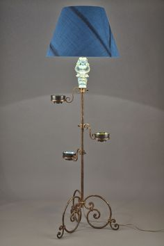 Wrought and gilded iron floor lamp, the stem decorated with a blue ceramic figure and three blue and green small bowls. It is resting on three scrolled feet.