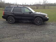 """2004 Java Black Forester XT with 1"""" lift and black rims, dark tint."""