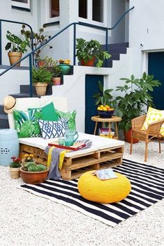 Materiais simples e muita cor compõem uma aconchegante varanda. - SOO 'YUMMY!' WITH POPS OF YELLOW, PALETTES USED FOR SEATING, ROWS OF PLANTS ON THE STAIRS.....SO INCREDIBLY BEAUTIFUL!!#️⃣