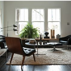 The juxtaposition of mid-century furniture and more rustic finds, including pieces from Africa and a collection of handmade pottery create a unique look. A shaggy rug provides additional contrast.