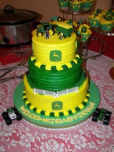 """John Deere Baby Shower Cake and Cupcakes - This cake was made for my brother-in law and sister-in law's baby shower celebrating the birth of their 3rd child finally a son. It is three tiers 10""""-8"""" and 6"""". It was iced in all buttercream icing in John Deere colors Green and Yellow. The topper used is toy John Deere tractor pulling a wagon. The middle tier has a plastic fence with plastic horses. I piped grass with buttercream icing and a shell border for bottom and top tier. I used John Deere…"""