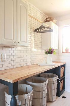 Gorgeous farmhouse laundry room with diy folding table with butler's block countertop, diy shiplap walls and white subway tile backsplash.