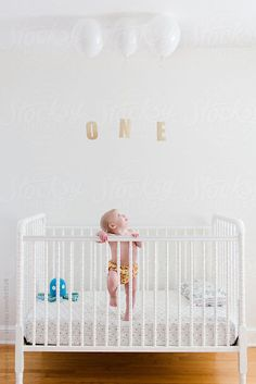 Cute baby standing in a crib on her first birthday with balloons and the word one by meaghancurry | Stocksy United