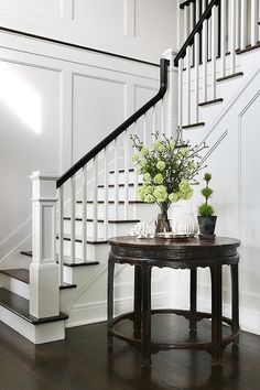 Chic foyer opens to a staircase fitted with white spindles and a black railing.