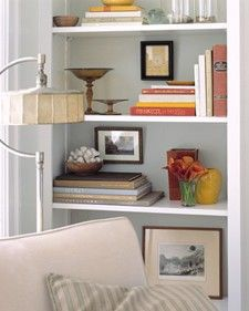 Create Depth. Along with layering your books and accessories on the shelves, add photos, artwork, or plates to the back of the bookcase to create a deeper and more visually appealing bookcase.