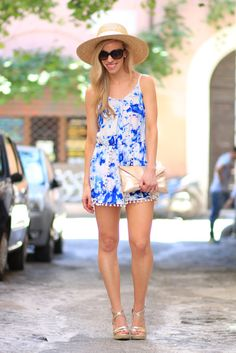 Pom Poms: blue watercolor romper with pom pom trim, J. Crew wide-brimmed straw hat, gold wedge sandals, Elaine Turner metallic clutch, romper summer outfit