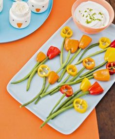 Veggie Flowers - For tulips, cut the tops off mini sweet peppers; for daisies, cut the mini pepper into ½-inchwide rings. Remove the seeds and use the knife to make a small hole in the bottom of the tulip or on one side of the ring. Insert string beans into holes, and serve with your favorite dip. #easter #spring