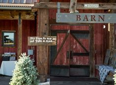 The Barn entrance with red wood, large doors and metal rustic sign