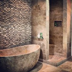 The luxurious all travertine bathroom. Hand carved tub with a while wall of stone and glass mosaics on the wall