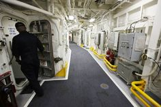 A sailor enters a doorway on the USS Zumwalt while at dock at the naval station in Newport, R.I.,