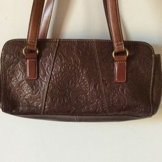 Very nice vintage embossed Fossil satchel Nice stamped floral brown leather Fossil satchel.  Very nice condition, clean inside and out.   Large zippered section in middle with open pouches on either side.   022905 Fossil Bags Satchels