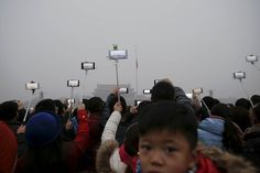 """People take videos during a flag-raising ceremony amid heavy smog at Tiananmen Square, after the Beijing issued its first ever """"red alert"""" for air pollution on December 9, 2015"""