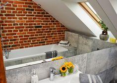 <p><strong>Łazienka na poddaszu</strong> stała się idealnym miejscem do wyeksponowania naturalnych materiałów, które nadają aranżacji ponadczasowy wyraz. <strong>Projekt łazienki</strong>, w której trio idealne stanowi surowa <strong>cegła na ścianie</strong>, zimny beton i wyjątkowo klimatyczne drewno, urzeka loftowym minimalizmem, który w odbiorze zachwyca naturalnym urokiem i wbrew pozorom - ciepłem.</p>