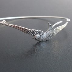 An antique silver finished brass swallow spreading his wings has been transformed into a delicate silver swallow bracelet with a silver filled