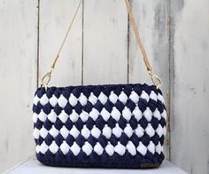 A classy bag with nice cool colours so reminiscent of Greek summer. Dark blue and white soft yarns harmoniously matched to weave this bag.  The long and elegant strap is made by natural cork with gold details.  It's length is adjustable with gilded metal fastener.   The bottom is also made by natural cork and elegantly bound with the main cotton body of the bag.   Height 21cm Length 25cm Width 8cm Price: 160€