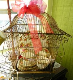 Vintage Plates in a Bird Cage with bow on top, lovely display