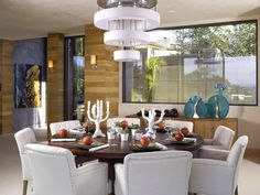 Repeat Design    Repetition is often used to create a unified space. A spiral chandelier echoes the round table in this dining room designed by Lori Dennis.