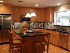 Kitchen remodel with wood floors, stainless steel appliances, granite countertops, and slate backsplash