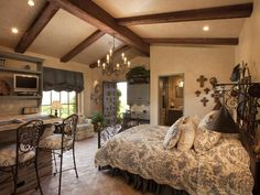 This large bedroom, which opens onto a courtyard area, includes a private eating and cooking area and bathroom. Wooden ceiling beams and blue and white details give the space a charming cottage atmosphere.