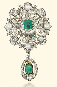 A VICTORIAN EMERALD, PEARL AND DIAMOND BROOCH Designed as a diamond-set openwork plaque of foliate motif accented by four pearls, mounted with a central rectangular-shaped emerald within an old-cut diamond surround, suspending an articulated emerald within a diamond-set open plaque, with pendant fitting, mounted in silver and gold, circa 1870, 6.0cm long