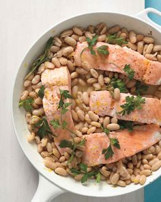 Creamy cannellini beans, sauteed with rosemary and lemon zest, provide a fragrant and delicious bed for steamed salmon in this easy and delicious weeknight meal.