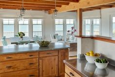 Breathtaking ocean views serve as the backdrop for this beach cottage kitchen. Natural wood cabinets match the wood ceiling and floors for a cohesive look and a sense of warmth. Nautical pendant lights are the perfect finishing touch.