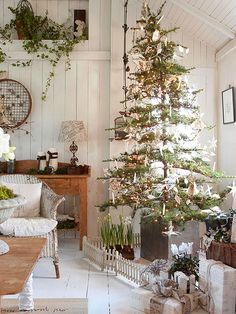 Delicate Christmas Tree... bhg.com A spindly tree looks best decked out in delicate paper ornaments.