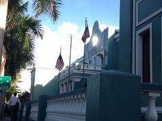 Escuela frente al Capitolio. Nos muestra las dos banderas pero en realidad esta mal puesta, porque se deja ver un palo entre las dos, lo cual sería incorrecto que pusieran otra bandera ahí, por eso es que debería de estar en el palo   de lado de la bandera de Estados Unidos de América.