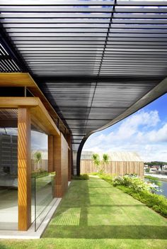 Meera House by Guz Architects - metal slat horizontal shading curves down to ground wood frame building