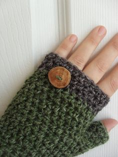 Crocheted fingerless mitts. not sure about the decorative only aspect of the large wooden button.