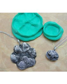 Custom paw print or puppy nose.. Instead of a necklace... Why not the Christmas tree?  Or maybe a frame with their pic.