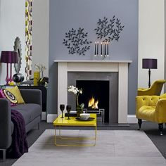 Bright colours, such as this lemon yellow, used sparingly with soft tones of grey and blue create a chic look. Mirrored alcoves create the illusion of more space and frame the fireplace, drawing the eye to it as a focal point.