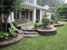 This landscaping design extends past the front porch and around both ends of the house.