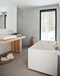 Une salle de bains anguleuse adoucie par le bois du plan vasque et la grande fenêtre