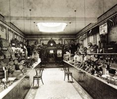 Sainsbury's Guildford High Street store on it's opening day, typical of the counter service shops opened by Sainsbury's from the 1890s until 1939. The tiled walls, marble topped counter and ceramic floor formed an instantly recognisable 'house style' which was functional as well as decorative - UK - 16 November 1906