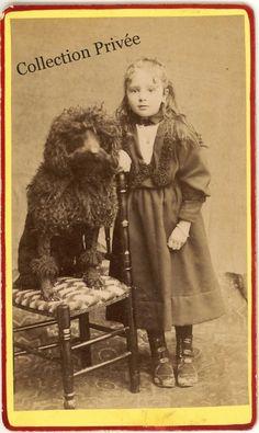 jouets d'enfants, jeux de photographes : Fillette avec un grand caniche sur une chaise. Pho...