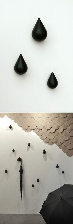 barra de madeira com ganchos para pendurar objetos, parede de tijolos a vista pintada de preto