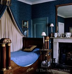 The spare bedroom has a mahogany lit bateau and blue patterned wallpaper in Lord Snowdon's home