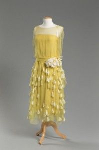 Evening Dress, designer unknown, purchased at Quinn-Maahs, Cleveland, about 1925 Yellow silk chiffon and taffeta  With its floating panels and appliquéd petals, this feminine dress was almost certainly intended for dancing. Though its designer is unknown, Phyllis Peckham purchased the dress from the Euclid Avenue retailer Quinn-Maahs, which was considered one of Cleveland's premiere shops for stylish women's fashions.