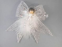 Sophia is an adorable little angel with a soft white marabou feather body flecked with silver thread and her wings are made of silver mesh ribbon. This sweet little angel is perfect as an ornament, on your holiday tree, on top of a wrapped birthday, teacher gift, or as a little party