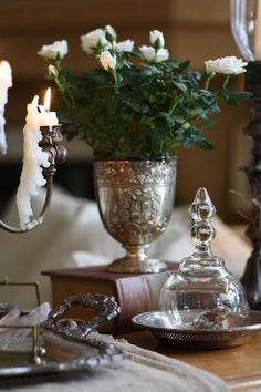 charming collected vignette with silver, dripping wax candles, varied height via books, flowers, texture