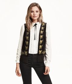 Vest in velvet with an embroidered pattern at front and no buttons. Fringe at hem.